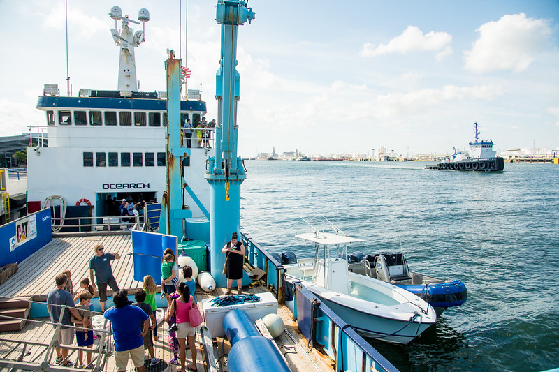 Mark Bowden(left) the Ocearch vessel's engineer. Informs touring families on how the crane operates when moving a hooked shark for research. Monday October 12, 2015.