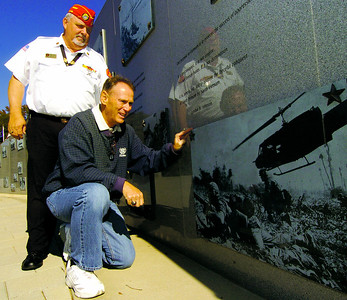 HENRY 11.10,11 ANCHOR 5 Marine Corps League of McDonough's Tom Oakes and retired Air Force Col. John Anzalone looks over images of the Vietnam War at The Veterans Wall Of Honor in McDonough. PHOTO BY JOE LIVINGSTON/STAFF