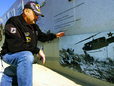 HENRY 11.10,11 ANCHOR 1 Vietnam Veteran Bill Steele looks over images from the Vietnam War at The Veterans Wall Of Honor in McDonough. PHOTO BY JOE LIVINGSTON/STAFF