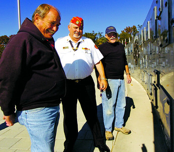 HENRY 11.10,11 ANCHOR 4 From left, retired Veteran Jim Joyce, Marine Corps League of McDonough's Tom Oakes and retired Naval Officer Maynard Robinson look over images of the Vietnam War at The Veterans Wall Of Honor in McDonough. PHOTO BY JOE LIVINGSTON/STAFF