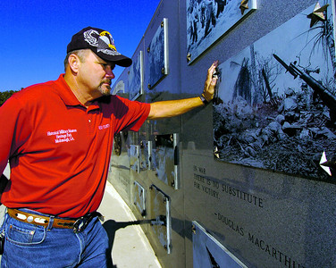 HENRY 11.10,11 ANCHOR 3 Vietnam Veteran Bill Steele looks over images from the Vietnam War at The Veterans Wall Of Honor in McDonough. PHOTO BY JOE LIVINGSTON/STAFF