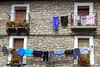 Clothes line hanging from stone wall houses