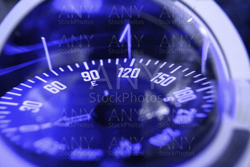 blue nautical compass closeup focus on east