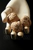 Mannequin wooden hand holding three walnuts