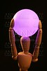 wooden mannequin holding  pink light ball on head