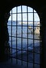 Blue sea behind the jail, arch window