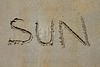 word sun spell on beach wet summer sand