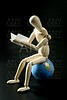 Wooden little mannequin deading sitting over the world map