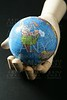 The world map in wood mannequin hand, black backgorund