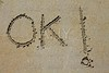 ok word spell written on beach wet sand