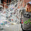 MJ Bujold creates massive bubbles on the streets of Lowell and brings simple happiness to pedestrians. SUN/Caley McGuane