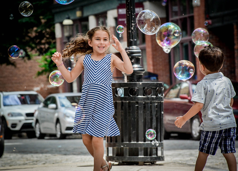 Sophie Silveira, 6, and her brother Mason, 3, of Peabody play in the streets of Lowell that are full of bubble created by MJ Bujold. SUN/Caley McGuane