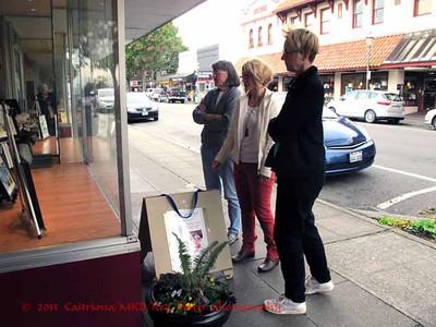 Michelle Abbott, Lynn Davis-Smith, and Teresa Lawton decide on the window display.