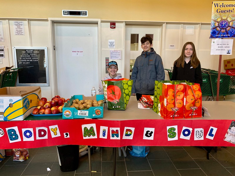 Left to right: Lizzie Johnson, Alex Savage and Grace Doyle, members of First Parish Church and MLK Day of Service volunteers, spend the morning preparing and distributing grab-and-go bags for community members in need. The bags include fresh fruits and vegetables, hygiene products and information on mindfulness activities designed to reduce stress and anxiety.