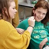 """GameLoft AmeriCorps Program member Thalia Sweeney (left) paints zombie makeup on a student (right) during The Game Loft's """"Emergency Preparedness for a Zombie Apocalypse"""" MLK Day of Service project.at The Game Loft's """"Emergency Preparedness for a Zombie Apocalypse"""" MLK Day of Service project."""