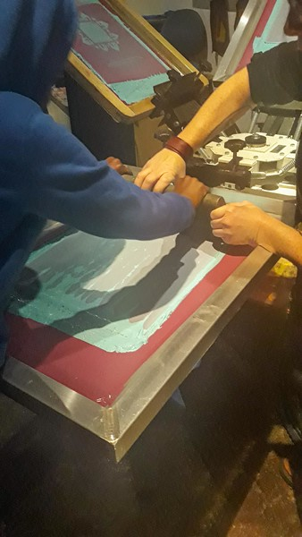 A student and a community volunteer work together to produce a screen print of original artwork honoring Dr. King's legacy and message.