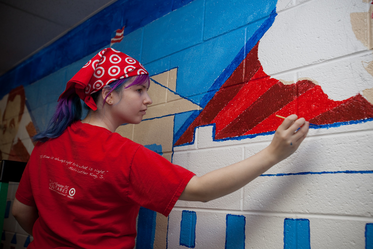 MLK Day, January 1 8, 2010: A volunteer paints details on a mural at TC Williams High School's Minnie Howard campus.