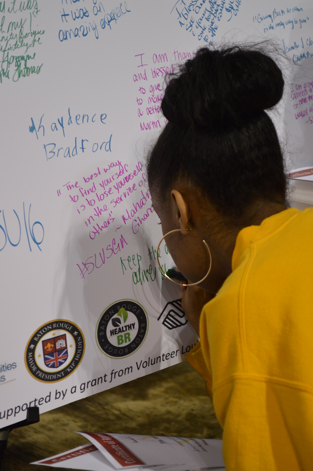 A young volunteer writes a reflection during the Capital Area United Way service event in Baton Rouge, LA on MLK Day 2014.