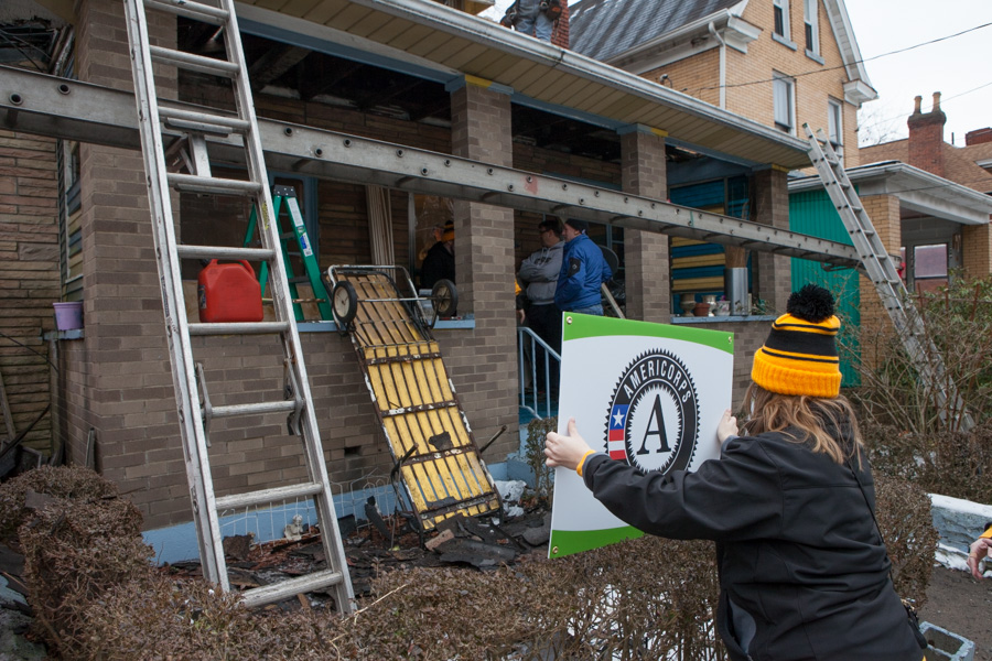 A volunteer displays an AmeriCorps sign outside a house being refurbished on MLK Day 2014. Photo by Henry Scott.