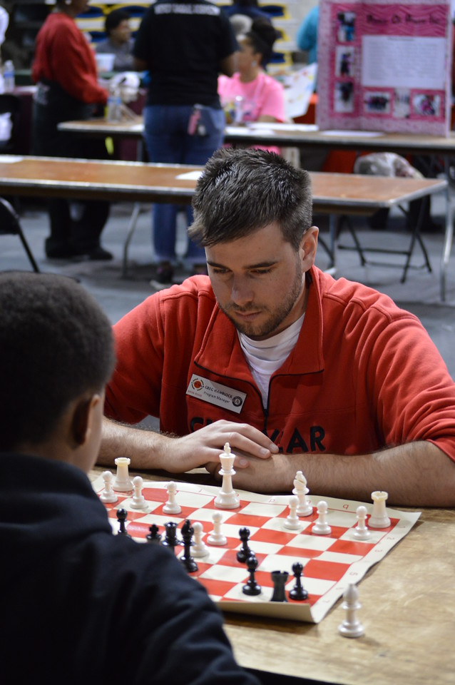 A City Year AmeriCorps member plays chess with a student at the Capital Area United Way service event in Baton Rouge, LA on MLK Day 2014.
