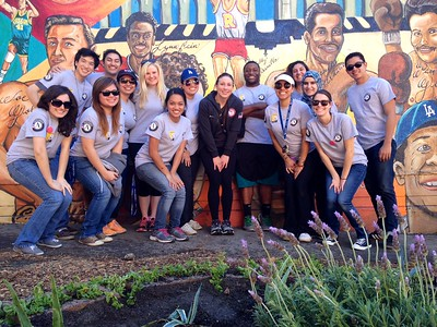 AmeriCorps members (pictured here with volleyball player Nicole Davis) and more than 300 volunteers painted an outdoor mural, refurbished basketball courts, built a community garden, and led a health fair for students at Roosevelt High School in Los Angeles, CA on MLK Day 2014.