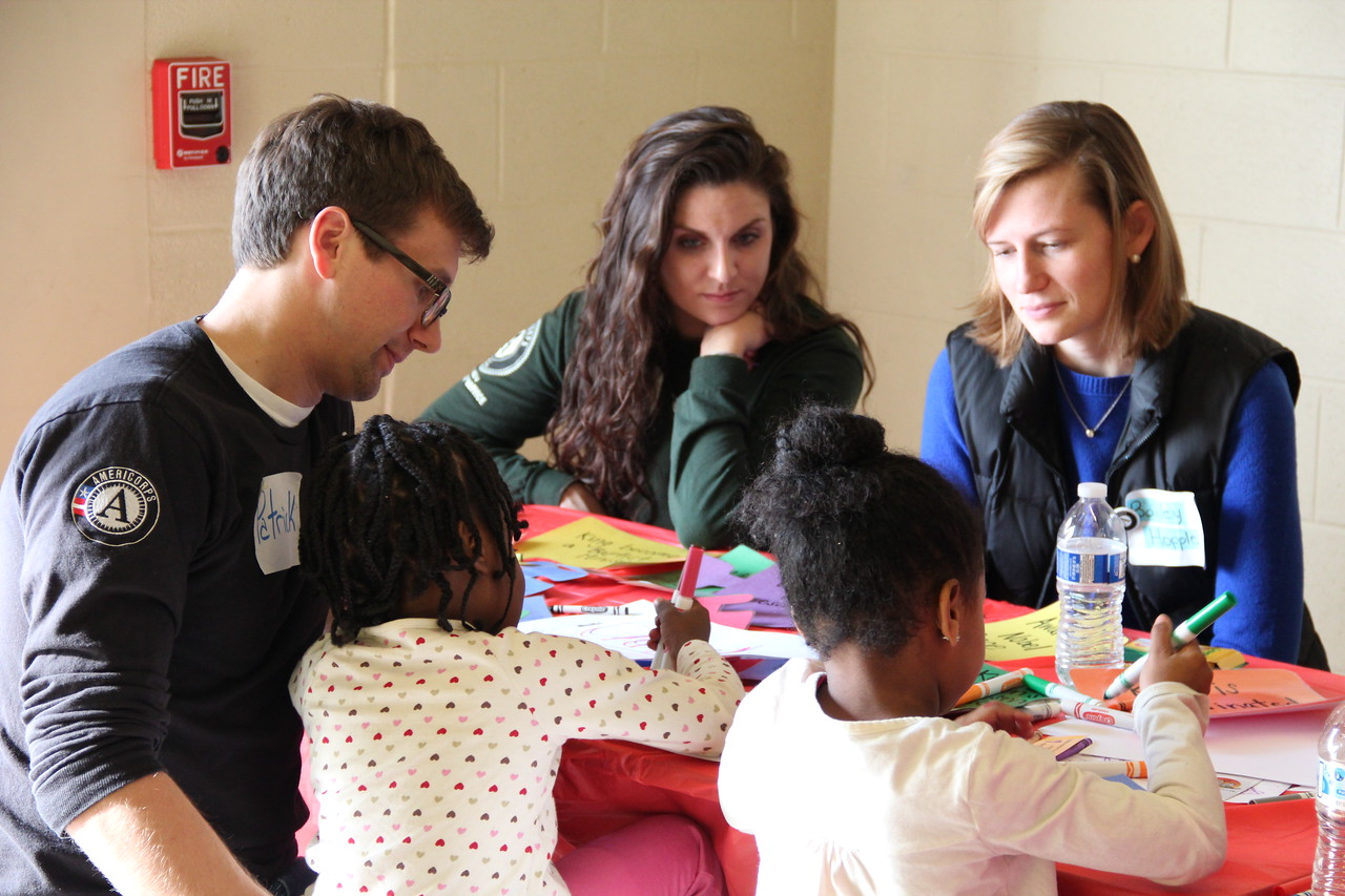 AmeriCorps members help young students on MLK Day 2014. Corporation for National and Community Service Photo.