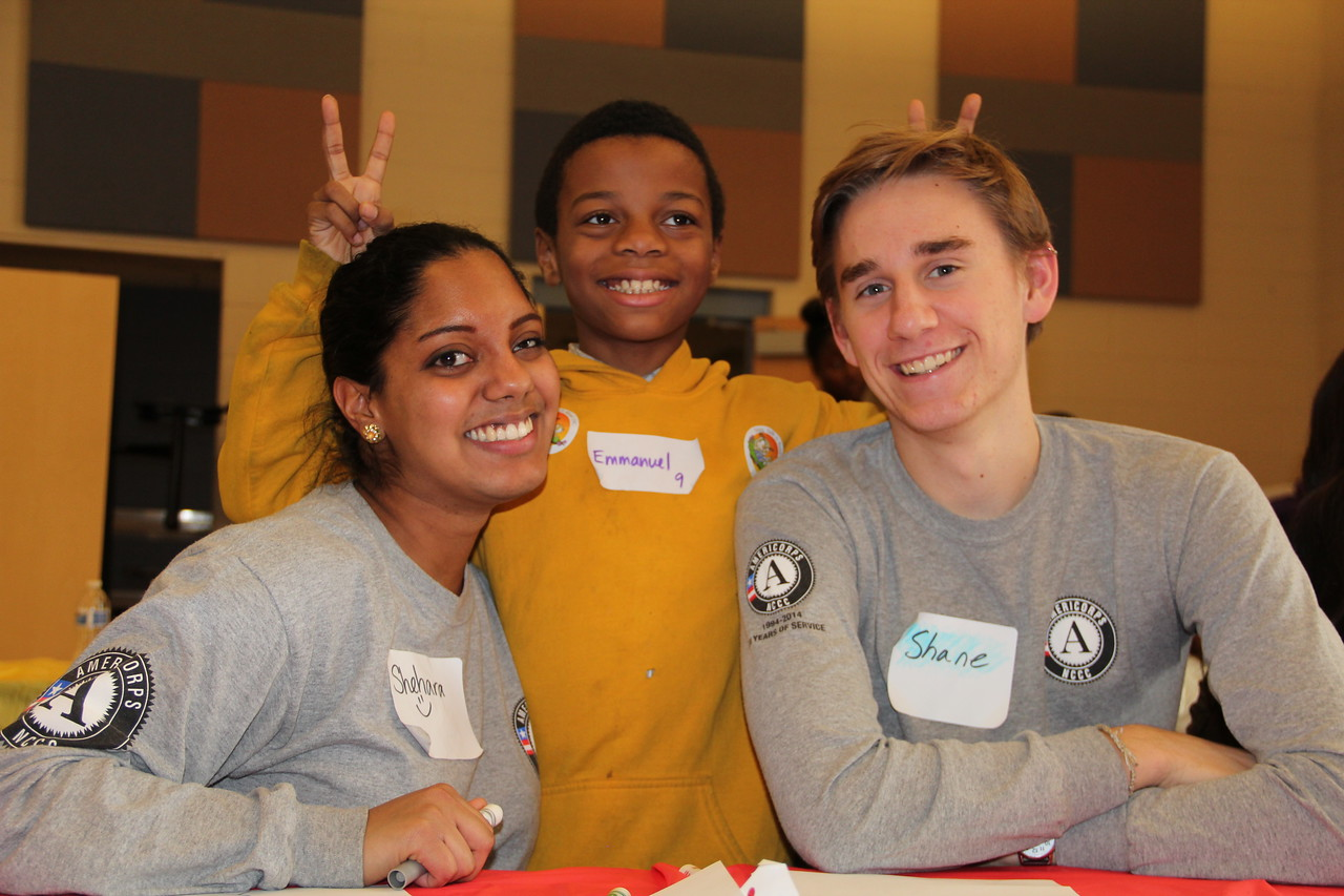 A young student with AmeriCorps NCCC members on MLK Day 2014. Corporation for National and Community Service Photo.