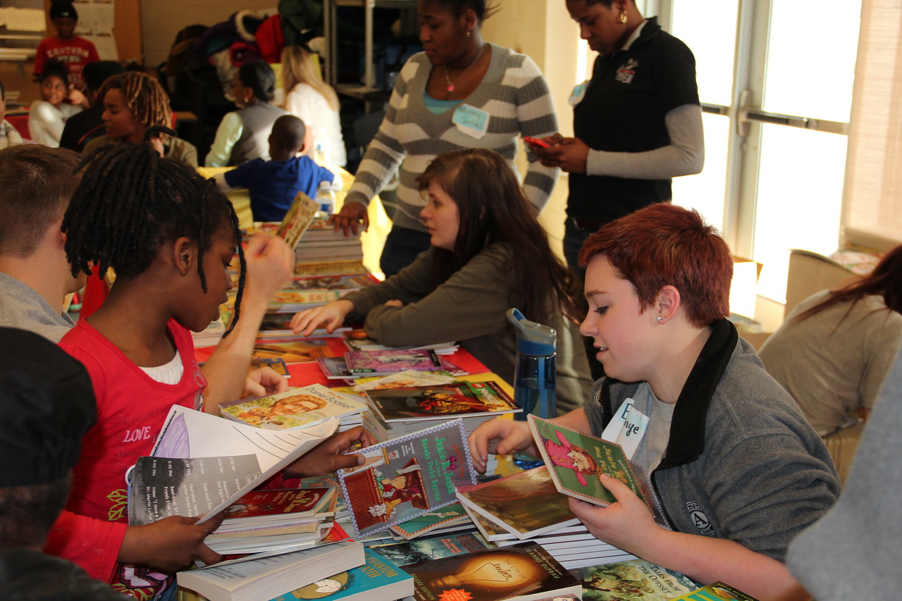 An AmeriCorps NCCC member helps a young student choose reading material at a book fair on MLK Day 2014. Corporation for National and Community Service Photo.