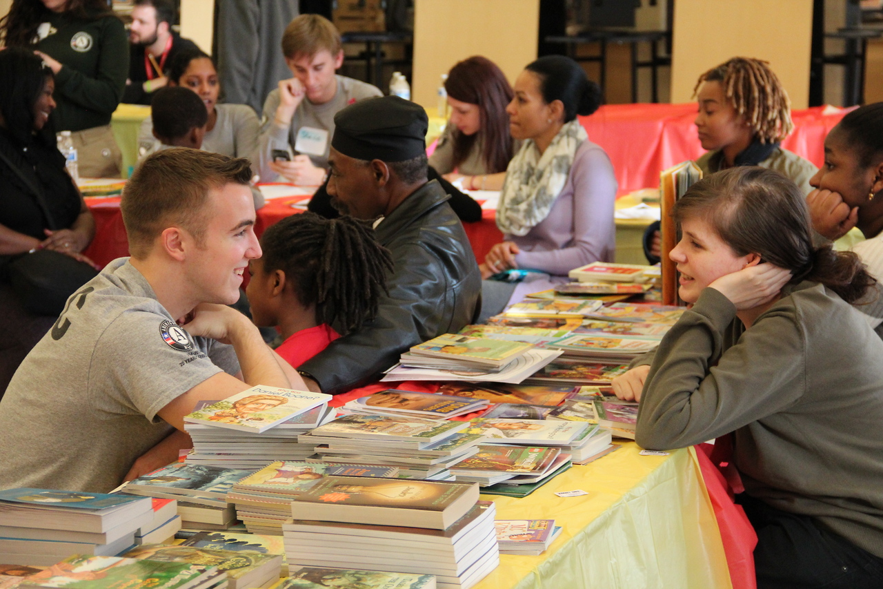 An AmeriCorps NCCC member and a community volunteer at a book fair on MLK Day 2014. Corporation for National and Community Service Photo.