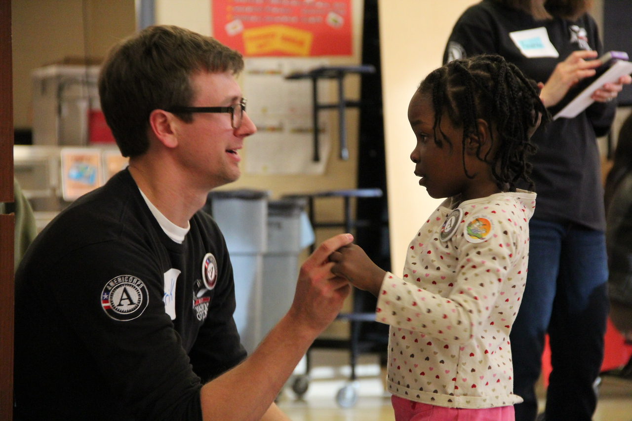 An AmeriCorps member with Metro DC Reading Corps talks to a young child on MLK Day 2014. Corporation for National and Community Service Photo.