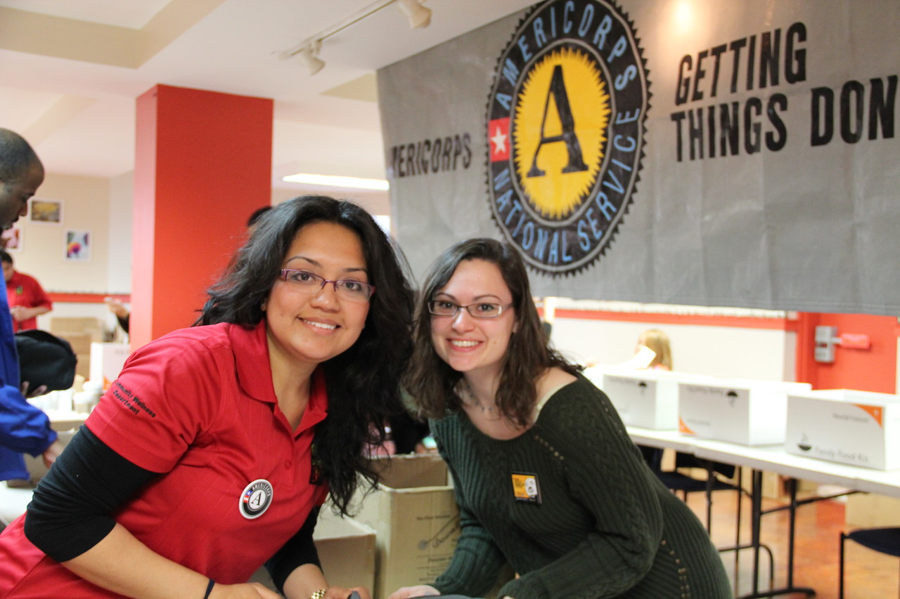 An AmeriCorps member and a community volunteer pose as they prepare hygiene kits for homeless youth at the Latin American Youth Center in Washington, D.C. on MLK Day 2014. Corporation for National and Community Service Photo.