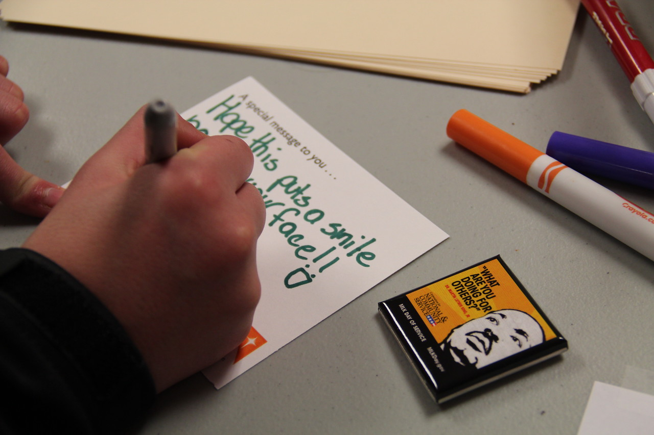 A volunteer writes a goodwill message to accompany hygiene kits for homeless youth at the Latin American Youth Center in Washington, D.C. on MLK Day 2014. Corporation for National and Community Service Photo.