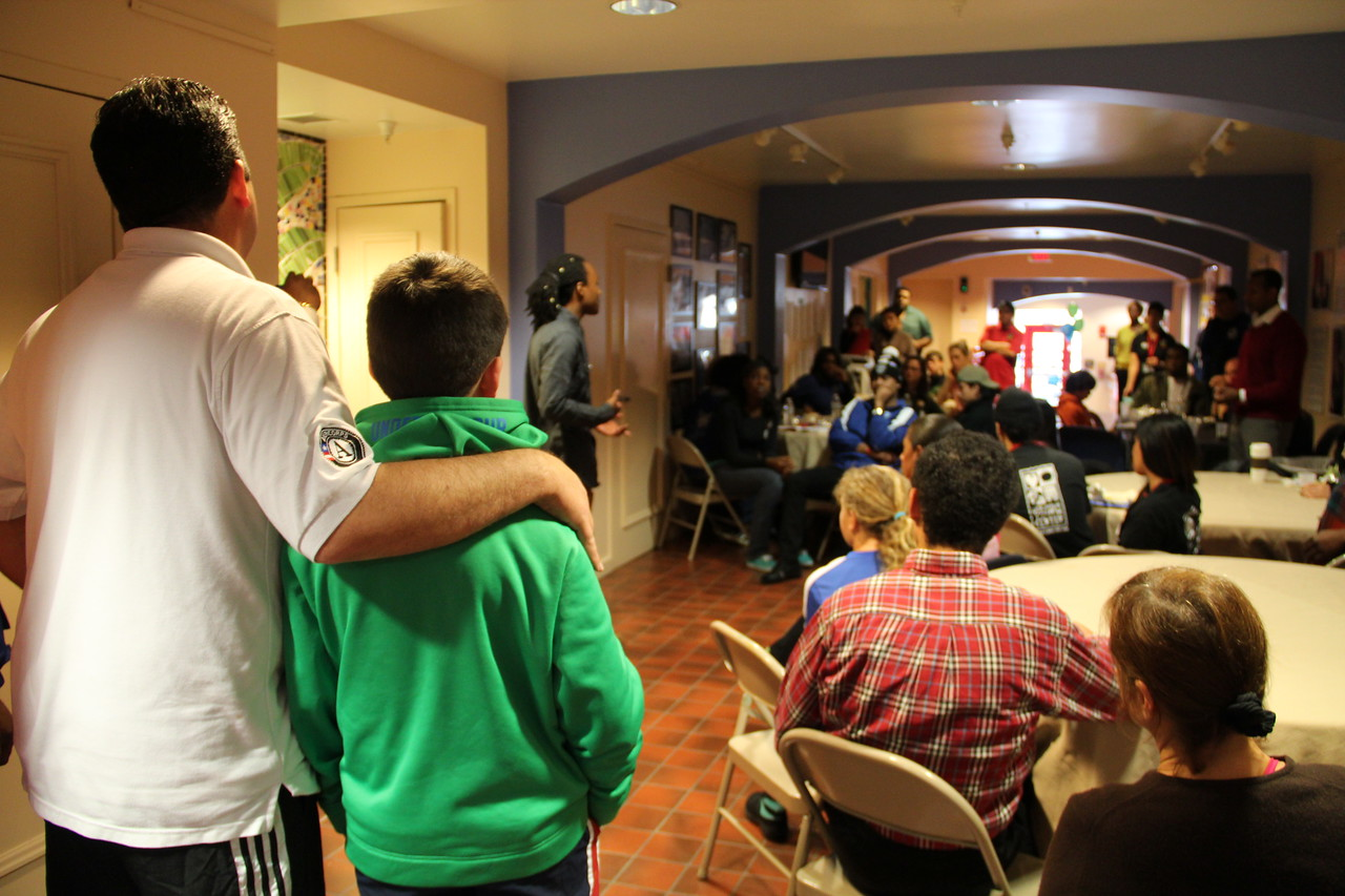 An AmeriCorps program coordinator and volunteers listen to a poetry performance at the Latin American Youth Center in Washington, D.C. on MLK Day 2014. Corporation for National and Community Service Photo.