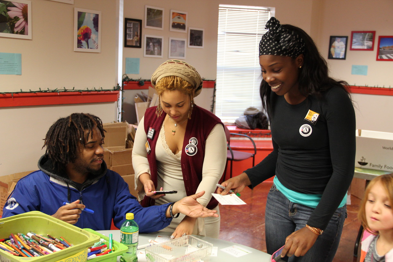 AmeriCorps members and an AmeriCorps alumna write goodwill messages to accompany hygiene kits for homeless youth at the Latin American Youth Center in Washington, D.C. on MLK Day 2014. Corporation for National and Community Service Photo.