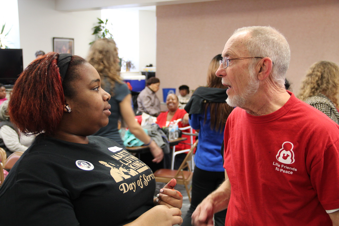 A volunteer chats with a representative of Little Friends for Peace on MLK Day 2014. Corporation for National and Community Service Photo.
