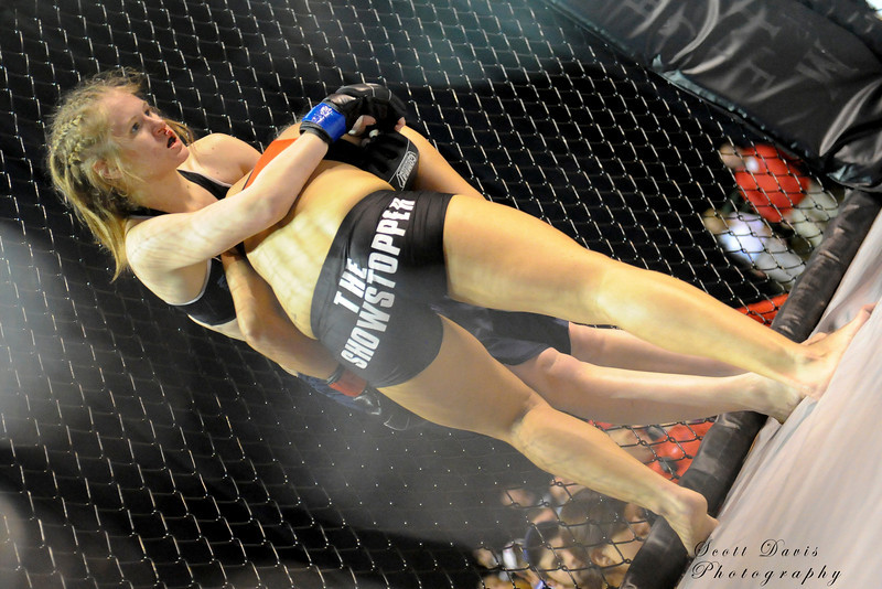 Lisa Reed drives Rita Myers into the cage during the American MMA Ohio Championships at US Bank Arena in Cincinnati,Ohio. during the American MMA Ohio Championships at US Bank Arena in Cincinnati,Ohio.
