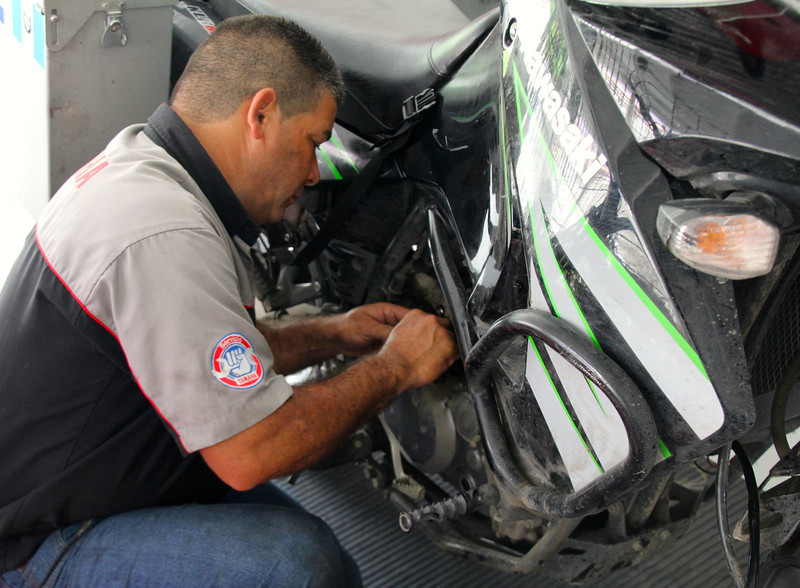 Day 21.  Any clues about how this day started off? <br /> <br /> A mechanic that Rodrigo found, hard at work on my clutch cable that was starting to fray during the many miles that I've ridden. - Conor