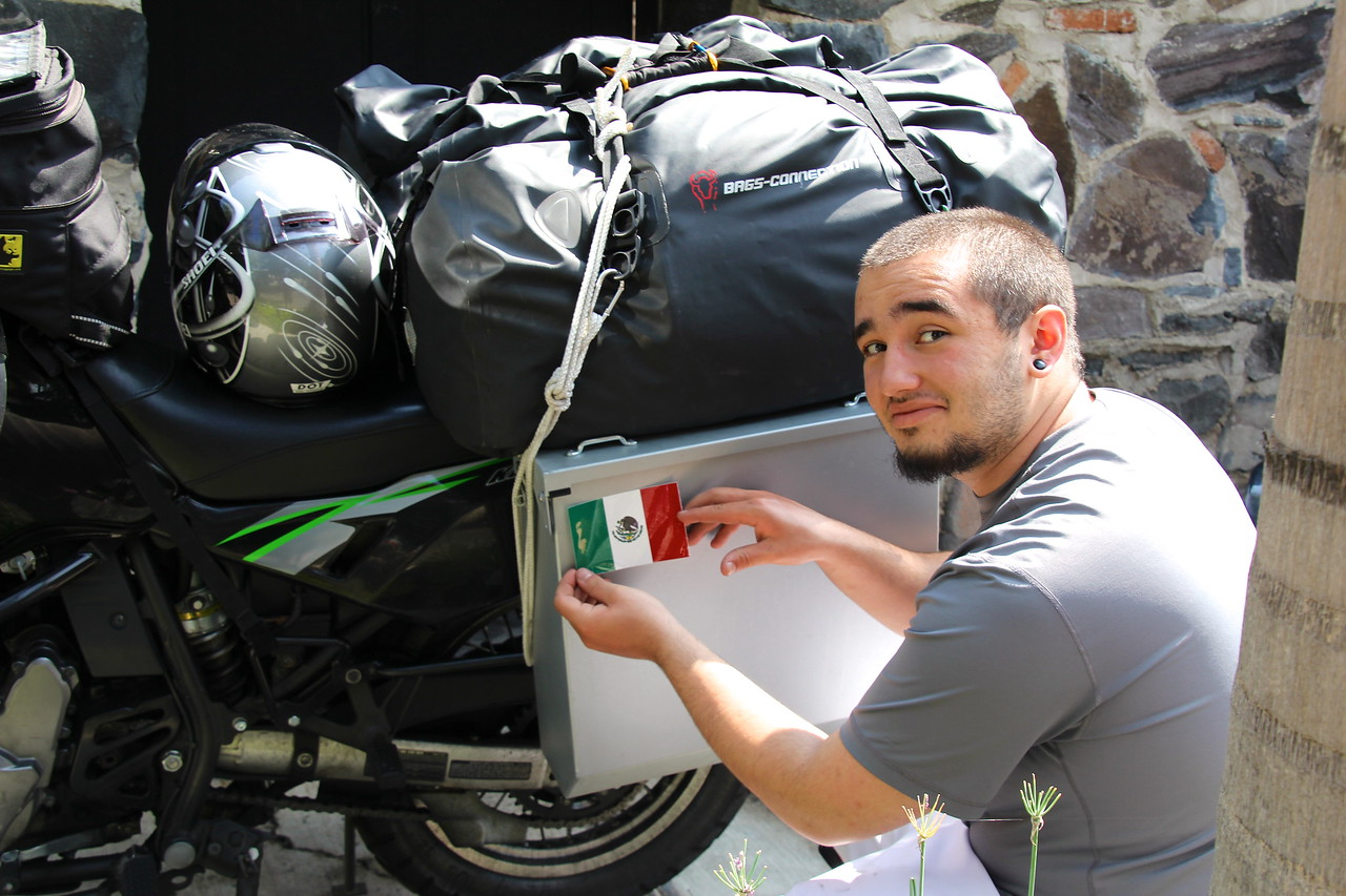 Here I am putting the first sticker on the pannier, this is a proud moment for me and I am pumped to continue to explore more of the continent on this adventure. - Conor