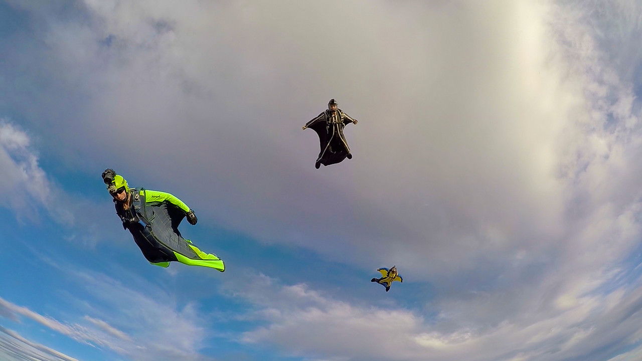 I am back flying and capturing the other wingsuit flyers as they prepare to stack alongside and over me.  Picture taken by Curt Vogelsang in Moab, UT during their annual event.