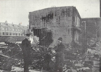 Posing in front of the ruins of his factory is Mr Emmett, who has recovered from the devastation a tin containing 150 shillings. The policeman may well be protecting him as few people could have had possession more valuable that this.