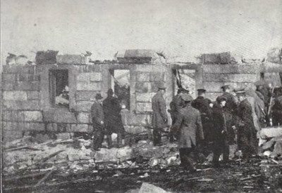 Soldiers and civilians search for bodies in the basement of a ruined school. It took weeks for all of the bodies to be recovered, not helped by the fact that no one was sure exactly how many they were looking for, due to the number of temporsry residents in the city and those bodies which had been destroyed by the explosion.