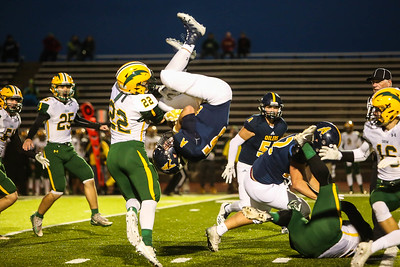 Mt. Pleasant's Zachary Mogg (15) holds onto the ball as he falls from being lifted over Midland Dow's Brennan Doyle (22) Friday, Oct. 12, 2018. Final 14-10 Mt. Pleasant. (PHOTOS BY KEN KADWELL--FOR MORNINGSUN.COM).