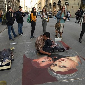 Awed by artists reproducing Renaissance masterpieces in chalk on a stone paved street.