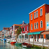 Murano island canal, colorful houses and boats, Venice, Italy.