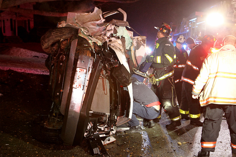 Leominster firefighters work to free a driver who was trapped in a vehicle after it struck a tree and rolled on its side early Saturday morning on Lowe Street. SENTINEL & ENTERPRISE / SCOTT LaPRADE