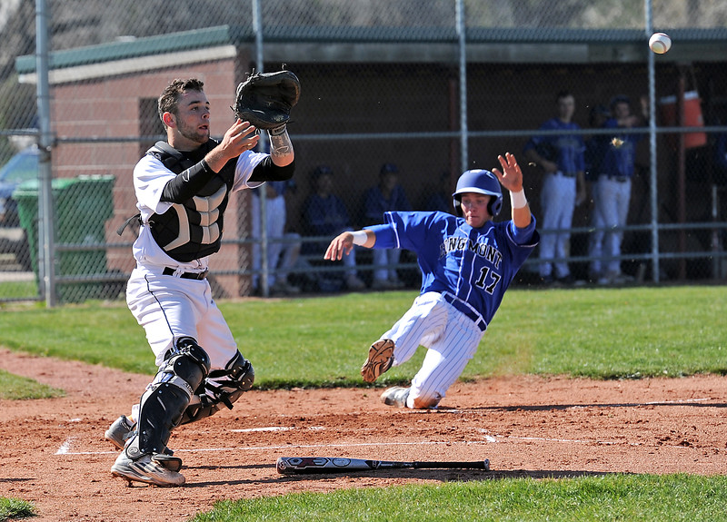 Mountain View's catcher Mike Felton tries to catch the ball at Longmont's #17 Andrew Voydat slides into home Monday, May 2, 2016, at Mountain View High School in Loveland. (Photo by Jenny Sparks/Loveland Reporter-Herald)