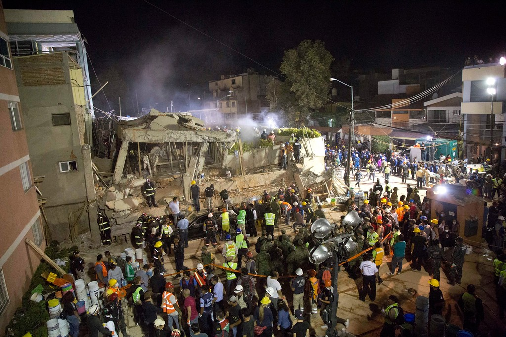 . Volunteers and rescue workers search for children trapped inside at the collapsed Enrique Rebsamen school in Mexico City, Tuesday, Sept. 19, 2017. The 7.1 earthquake stunned central Mexico, killing more than 100 people as buildings collapsed in plumes of dust as rescue efforts took place at the school in southern Mexico City, where a wing of the three-story building collapsed into a massive pancake of concrete floor slabs killing scores of students. (AP Photo/Gerardo Carrillo)