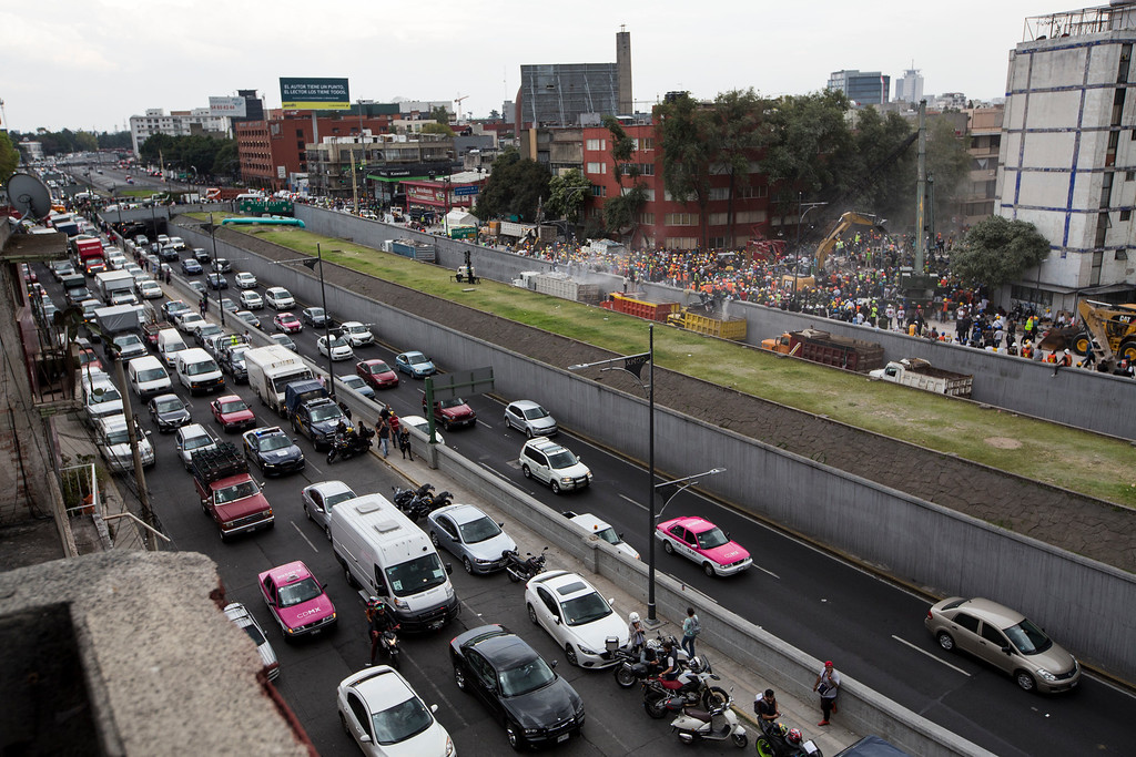 . Rescue personnel work on a collapsed building, far right, as vehicle traffic crawls on the Viaducto highway, a day after a devastating 7.1 earthquake, in the Del Valle neighborhood of Mexico City, Wednesday, Sept. 20, 2107. Efforts continue at the scenes of dozens of collapsed buildings, where firefighters, police, soldiers and civilians continue their search to reach the living. (AP Photo/Moises Castillo)
