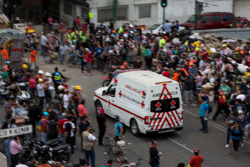 . A Mexican Red Cross ambulance arrives to a zone where a building collapsed, a day after a devastating 7.1 earthquake, in the Del Valle neighborhood of Mexico City, Wednesday, Sept. 20, 2107. Efforts continue at the scenes of dozens of collapsed buildings, where firefighters, police, soldiers and civilians continue their search to reach the living. (AP Photo/Moises Castillo)