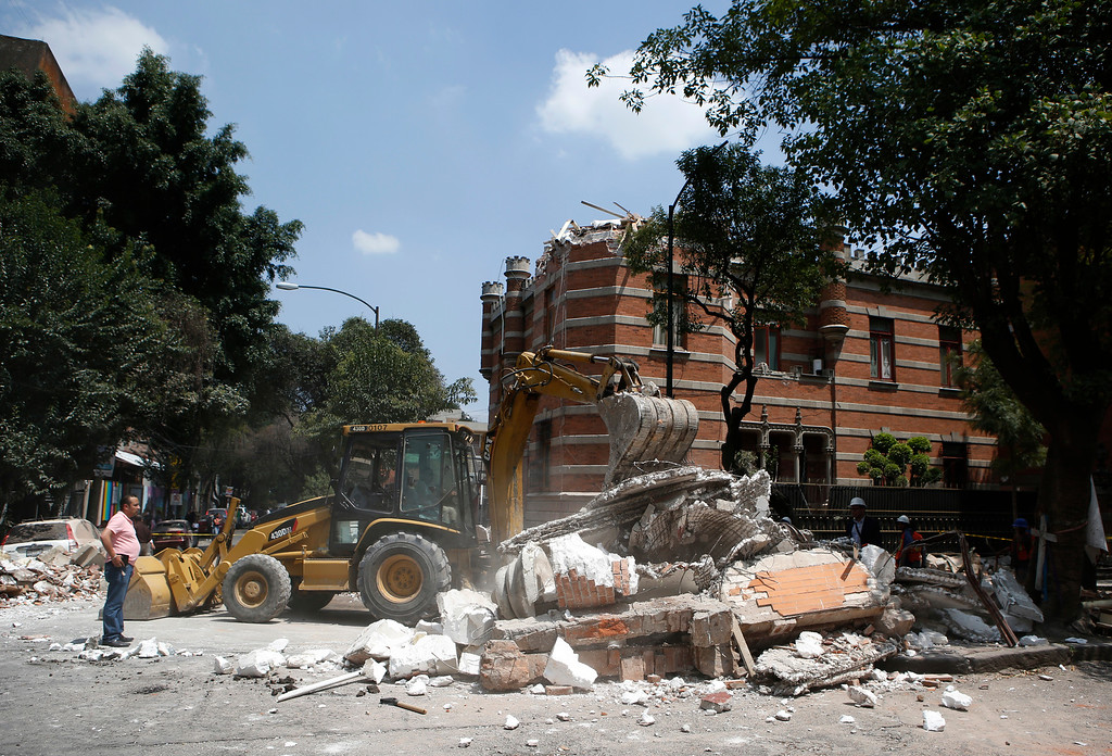 . A bulldozer removes debris from a partially collapsed building after an earthquake in Mexico City, Tuesday, Sept. 19, 2017. A powerful earthquake jolted central Mexico on Tuesday, causing buildings to sway sickeningly in the capital on the anniversary of a 1985 quake that did major damage. (AP Photo/Rebecca Blackwell)
